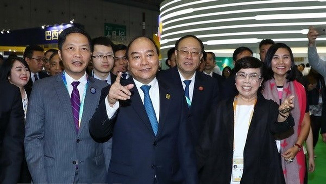 Prime Minister Nguyen Xuan Phuc (second from left) visits Vietnam's national stall at China International Import Expo 2018 (Source: VNA)