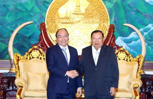 Prime Minister Nguyen Xuan Phuc (L) met General Secretary of the Lao People's Revolutionary Party and President of Laos Bounnhang Vorachith on February 5 (Photo: VNA)