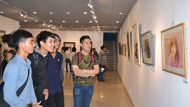 Visitors admiring paintings on display at the exhibition