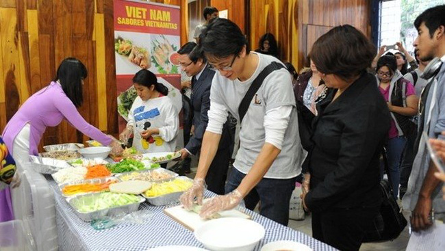 A student is making Vietnamese spring rolls at the event. (Photo: VNA)