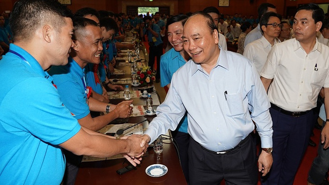 PM Nguyen Xuan Phuc shakes hands with the workers at the dialogue. (Photo: VGP)