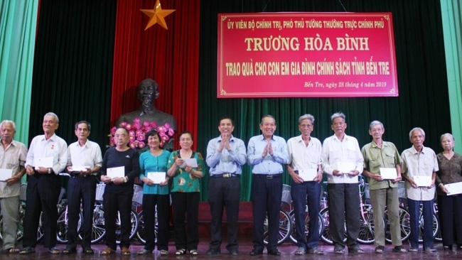 Permanent Deputy PM Truong Hoa Binh (sixth from right) presents gifts to policy beneficial families in Ben Tre province.