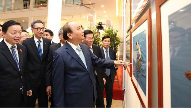 Prime Minister PM Nguyen Xuan Phuc joins other delegates to admire photos on display at the exhibition (Photo: hanoimoi.com.vn)