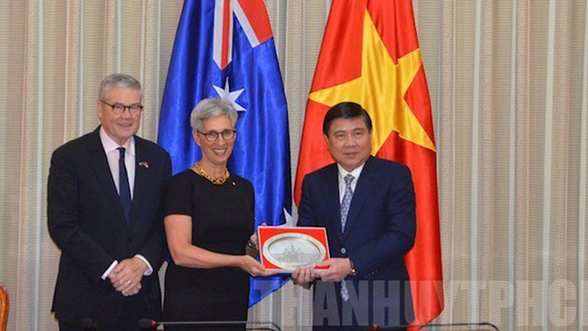 Chairman of the Ho Chi Minh City People's Committee Nguyen Thanh Phong (R) presents a souvenir to Governor of Australia's Victoria state Linda Dessau.