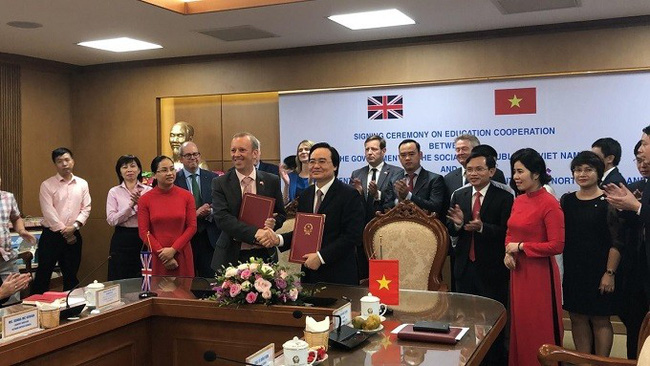 Vietnamese Minister of Education and Training Phung Xuan Nha (R) and Ed Vaizey, Trade Envoy of the UK Prime Minister, sign the MoU on educational cooperation between the two governments. (Photo: UK Embassy)
