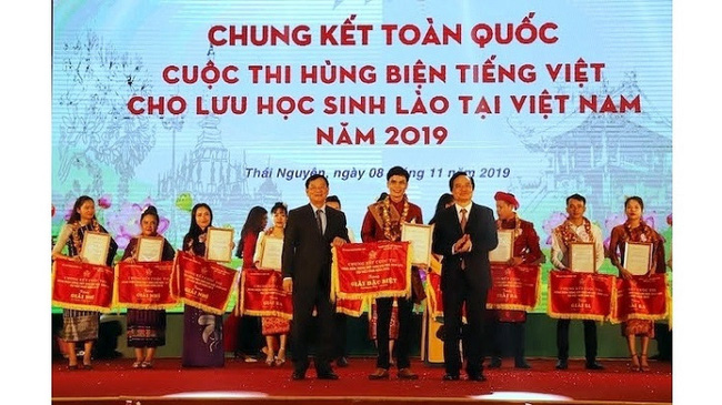 Minister of Education and Training Phung Xuan Nha (R) and President of Vietnam-Laos Friendship Association Tran Van Tuy (L) presented the special prize to winner Boun Soukhaluck (C) at the final round. (Photo: NDO/The Binh)