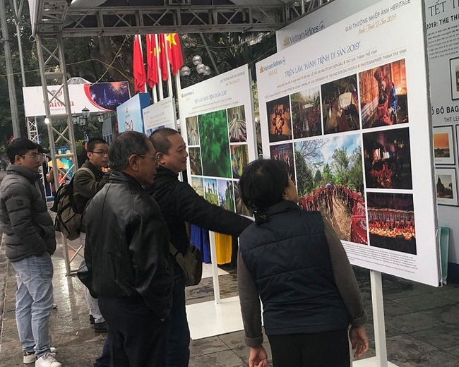 Visitors admire the photos on display at the exhibition. (Photo: baotintuc.vn)