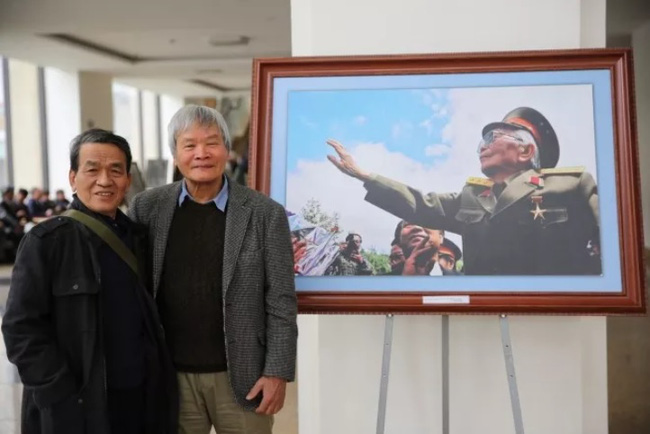 Journalists Nguyen Dinh Toan (right) and Tran Dinh beside the photo titled 'General Vo Nguyen Giap waving to Dien Bien for the last time'. (Photo: thethaovanhoa.vn)
