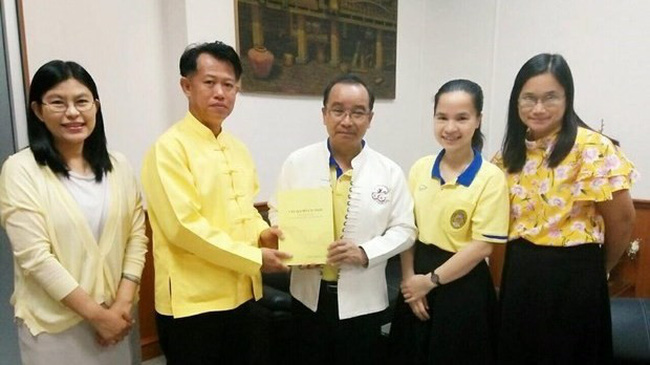 Dr. Boonlue Chaimano, head of the Thai language department under the Lampang Rajabhat University, presents the book to Associate Prof. Dr. Somkiat Saithanoo, head of the university. (Photo: VNA)