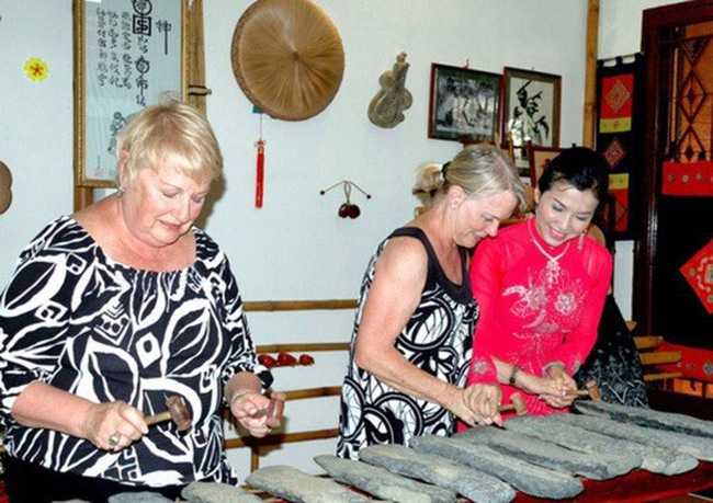 Meritorious Artist Tuyet Mai shows international tourists how to play a traditional Vietnamese musical instrument at Truc Mai Home Concert. (Photo courtesy of www.nld.com.vn)