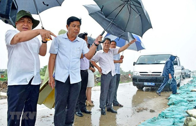 Minister of Planning and Investment Nguyen Chi Dung (L) inspects landslide points along a sea dyke route in Ca Mau province (Source: VNA)