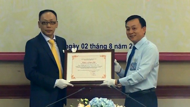 Director of Ho Chi Minh Museum, Dr Vu Manh Ha (R) presents a letter of gratitude to Vuong Quynh Xuan for his family's donation of two valuable pieces of Uncle Ho's memorabilia to the museum. (Photo: VTV)