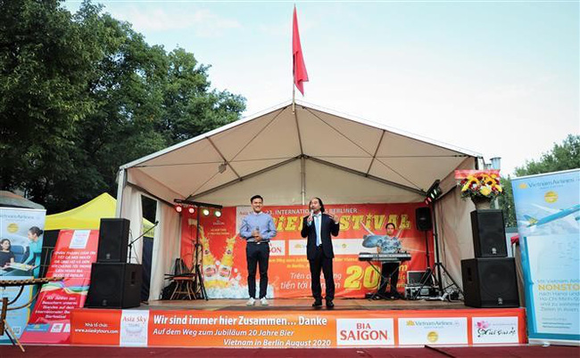 Director of Asia Sky Tours Nguyen Xuan Hung (R) speaks at the Vietnamese pavilion in the 23rd International Berlin Beer Festival. (Photo: VNA)