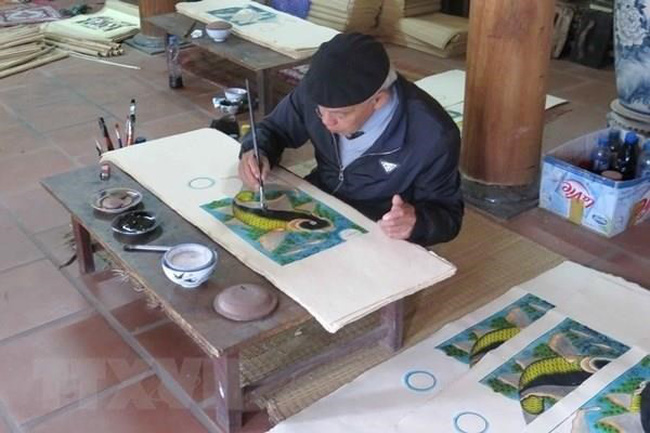 An artisan finishes a Dong Ho painting (Photo: VNA)
