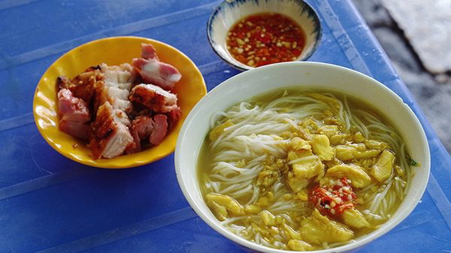 A bowl of Chau Doc fish noodle soup is served along with a plate of roasted pork and a bowl of fish sauce. (Photo: VnExpress/Phong Vinh)