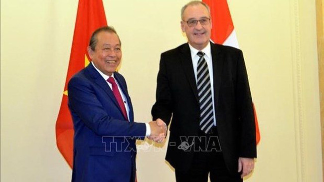 Permanent Deputy Prime Minister Truong Hoa Binh (L) and Vice President and head of the Department of Economic Affairs, Education and Research of Switzerland Guy Parmelin (Photo: VNA)