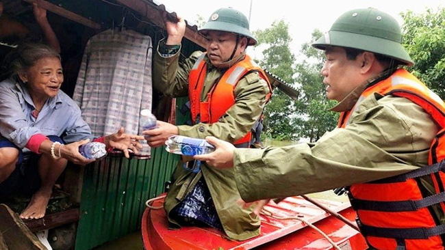 A Quang Binh resident receives water bottles from local leaders.