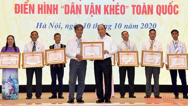 Prime Minister Nguyen Xuan Phuc (R) presents certificates of merit to exemplary models from the mass mobilisation movement at the event