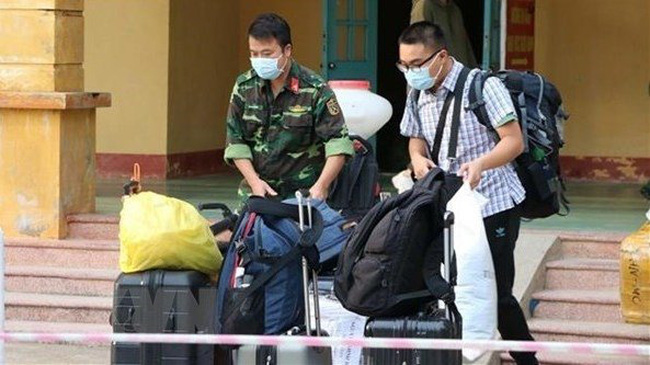 A soldier helps a citizen handle luggage at a military-managed quarantine site (Photo: VNA)