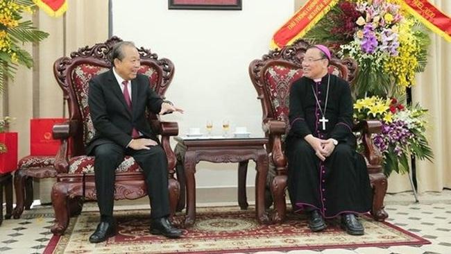 Permanent Deputy Prime Minister Truong Hoa Binh (L) extends Christmas greetings to Archbishop of the Hanoi Archdiocese Joseph Vu Van Thien (Photo: VNA)