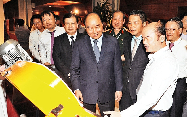 Prime Minister Nguyen Xuan Phuc (C) visits a booth introducing products by Vietnam's mechanical engineering industry. (Photo: NDO/Tran Hai)