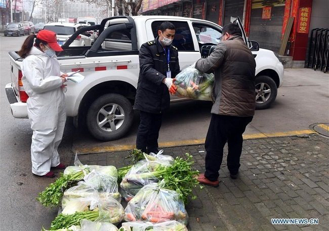 Staff members handle a bag of vegetables to a citizen in Guangshan County, central China's Henan Province, Feb. 7, 2020. Guangshan County, located on the border of Henan and Hubei, conducts strict prevention and control measures during the battle against the novel coronavirus epidemic. Local authorities have coordinated and established Wechat groups, so as to enable vegetable supply based on specified demands. (Photo: Xinhua)