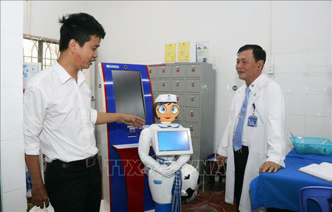Vo Hong Quan, Director of the Centre of Information and Technology of the Eastern People Military Hospital in HCM City (left), introduces the nurse robot named Tam. (Photo:VNA)