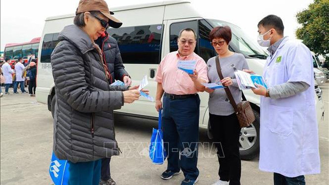 A medical worker delivers leaflets on Covid-19 for visitors to Ha Long Bay, Quang Ninh Province (Photo: VNA)