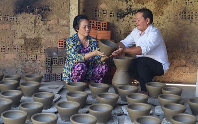 Artisan Dang Van Trinh and his wife, Pham Thi Thu Cuc, checking the quality of their pottery products (Photo: Lam Uyen)