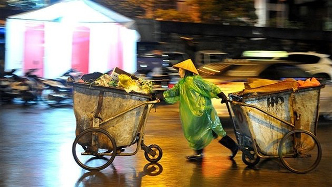 A worker of the Hanoi Urban Environment Company (URENCO) moving garbage carts on Lunar New Year's Eve.