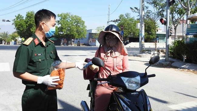 A soldier from Thuan Nam District Military Command (Ninh Thuan province) provides free masks to a local person while entering the isolated area in Van Lam 3 hamlet, Phuoc Nam commune. (Photo: NDO/Nguyen Trung)