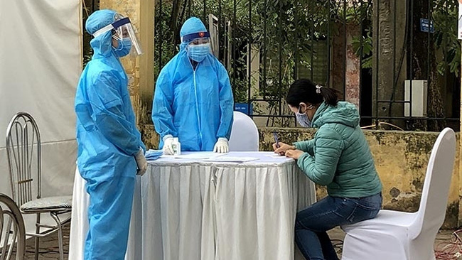 People declare their health information at a field rapid test station in Hanoi's Dong Da District.