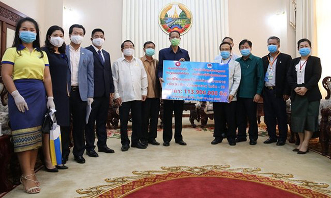 The Vietnamese community in Laos present US$13,000 to the Lao government on April 10 to support the country's fight against COVID-19. (Photo: NDO)