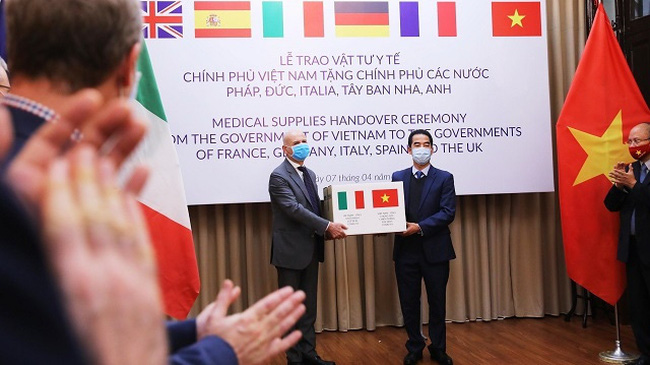 Vietnamese Deputy Foreign Minister To Anh Dung (R) handed a symbolic token representing the gift of 111,000 anti-bacterial masks from the Vietnamese Government to Italian ambassador Antonio Alessandro, Hanoi, April 7, 2020. (Photo: VNA)