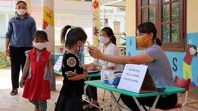Children at Mu Sang Kindergarten in Phong Tho District, Lai Chau Province have their temperatures checked as the facility reopening after the three-month break due to the coronavirus pandemic. (Photo: NDO/Tran Tuan)