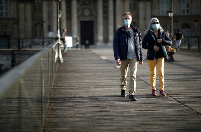 People wearing protective masks walk at the Pont des Arts bridge during the outbreak of the coronavirus disease (COVID-19) in Paris, France, May 2, 2020. (File photo: Reuters)