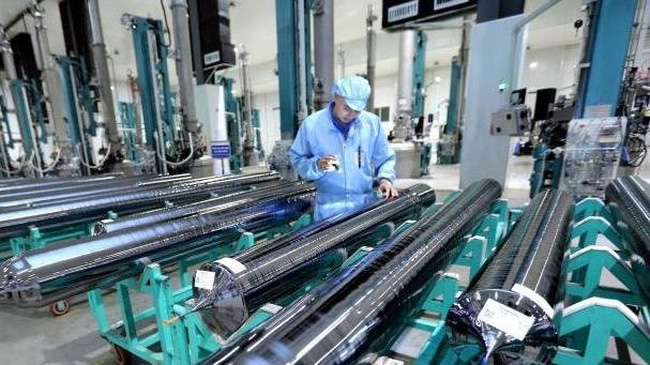 A worker inspects materials for producing solar batteries at JA Solar Vietnam Co., Ltd. in Quang Chau Industrial Park, Bac Giang Province. (Photo: VNA)