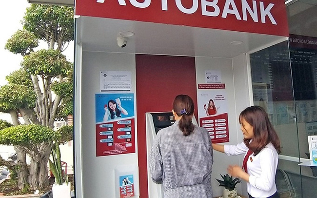 An employee of the Agribank branch in Duc Hoa district, Long An province is instructing a customer to perform steps to deposit money into an ATM.