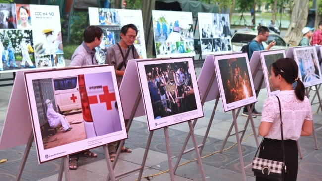 Visitors admiring photos on display at the exhibition (Photo: VNA)