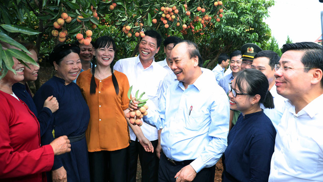 PM Nguyen Xuan Phuc talking with officials, employees and local people at the Uncle Ho fruit garden. (Photo: VGP)