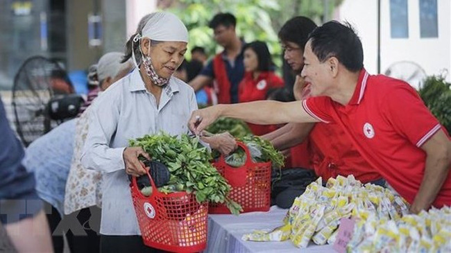 Residents in difficult circumstances shop at a humanitarian market hosted by the Vietnam Red Cross Society (Photo: VNA)