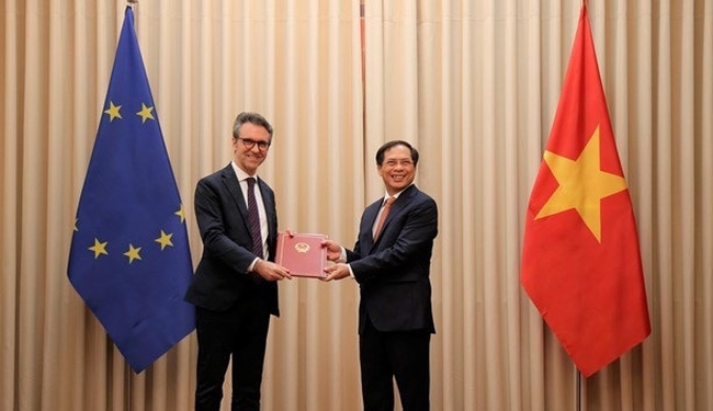 Deputy Foreign Minister Bui Thanh Son (R) hands over the dilomatic notes to head of the EU Delegation to Vietnam, Ambassador Giorgio Aliberti on June 18 (Photo: VNA)