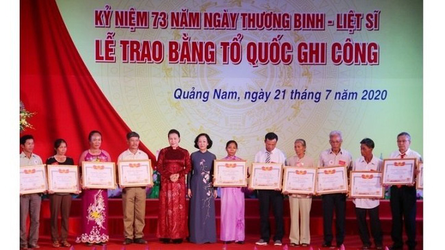 NA Chairwoman Nguyen Thi Kim Ngan (fifth from left) and Head of the Party Central Committee for Mass Mobilisation (sixth from left) present the Fatherland Remembrance Certificate to relatives of martyrs at the ceremony. (Photo: NDO/Tan Nguyen)
