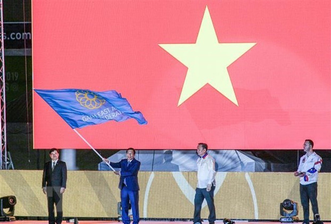 Minister of Culture, Sports and Tourism Nguyen Ngoc Thien receives the flag for the next hosting of the SEA Games 31 and ASEAN Para Games 11 at the closing ceremony of SEA Game 30 in the Philippines on December 11, 2019 (Photo: VNA)