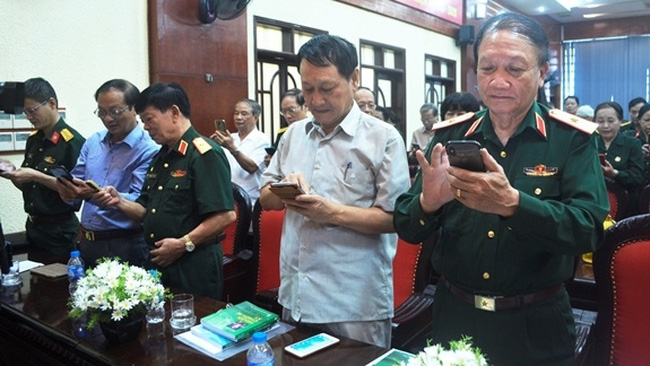 Delegates send text messages to support former Truong Son soldiers at the launching ceremony (Photo: qdnd.vn)