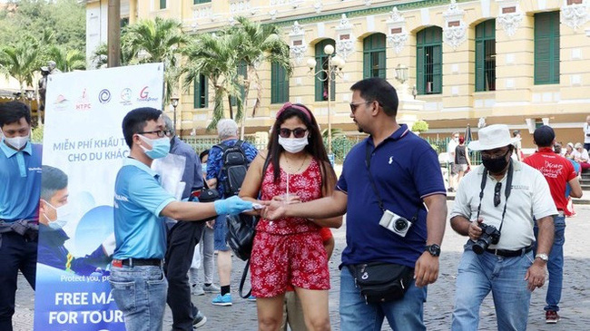 A staff of Ho Chi Minh City's tourism sector delivers free face masks to visitors in the city (Photo: VGP)