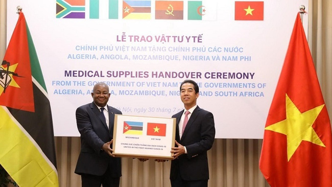 Deputy Foreign Minister To Anh Dung (R) presents medical supplies to a representative from Mozambique to support the country in fighting against COVID-19. (Photo: VNA)