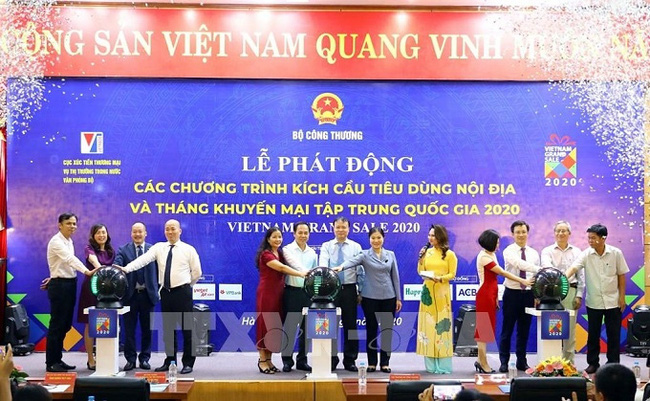 Delegates perform the ritual to launch domestic consumption stimulus programmes and a concentrated national promotion month on July 1. (Photo: VNA)