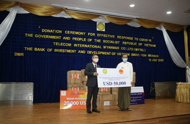 Vietnam Ambassador Ly Quoc Tuan (L) presents US$50,000 as a gift of the Vietnamese Government to Myanmar. (Photo: VOV)