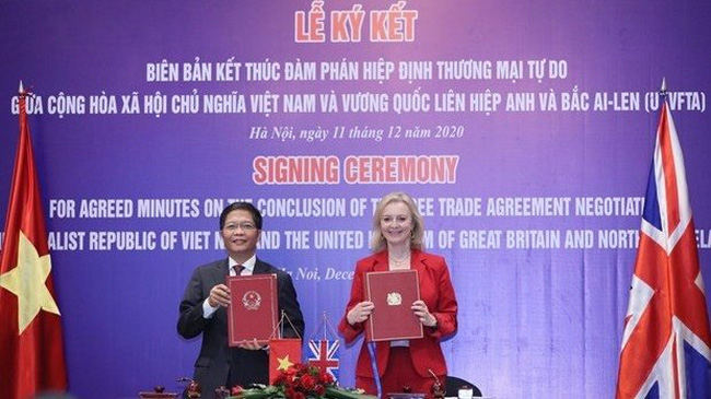 Minister of Industry and Trade Tran Tuan Anh and UK Secretary of State for International Trade Elizabeth Truss sign the minutes on the conclusion of negotiations over the UKVFTA. (Photo: VNA)